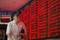 An elderly investor watches stock prices in China as markets in Hong Kong and Shanghai were weaker on Tuesday. Photo: Xinhua