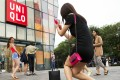 A Chinese woman poses for photo outside the Uniqlo flagship store where a steamy video purportedly taken inside one of its fitting rooms showing a couple apparently having sex in Beijing. Photo: AP