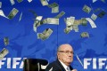 Comedian Simon Brodkin (unseen) throws fake dollars at Blatter. Photo: Reuters