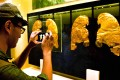 A visitor at the museum takes a picture of some of the gold ornaments returned to China. The pieces date back to about the 8th century BC. Photo: AFP