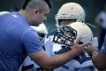 Coach Wes de Kirby gives last-minute instructions to player Liu Jiayou, 9, right, just before the start of their American football game in Beijing earlier this month. Photo: AP