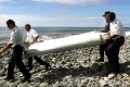 French gendarmes and police carry a large piece of plane debris which was found on the beach in Saint-Andre. It was supposedly headed for a testing centre in Toulouse, France, last night. Photo: EPA