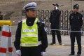 Police officers stand guard outside a Beijing court during a Chinese rights activist's hearing last year. Photo: Reuters