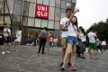 A couple take a selfie outside the Uniqlo flagship store where a steamy video was purportedly taken inside a fitting room in Beijing. The authorities are cracking down on home-made sex videos. Photo: AP