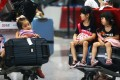 Children sit on luggage carts at Beijing Capital International Airport after flights were cancelled due to bad weather. Photo: AP