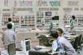 Workers in the main control room reactivate the No. 1 reactor at Kyushu Electric Power Co.'s Sendai nuclear plant. Photo: Kyodo