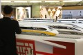 An Indonesian man photographs models of China Railway High-speed (CRH) trains, prepared for an exhibition which will open this week. Photo: AP
