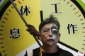 A protester at a rally for workers' rights seeks to ensure standard working hours in HK.Photo: AP