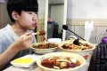 Kim Sung-jin, 14, broadcasts himself eating delivery Chinese food in his room. Photo: AP