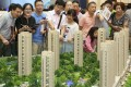 Customers look at a model of Longfor Properties project in Zhejiang province in China. Photo: Reuters