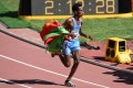 """Wrapped in the Eritrean flag, Ghirmay Ghebreslassie races to victory in the men's marathon at the """"Bird's Nest"""" National Stadium in Beijing. Photo: AFP"""