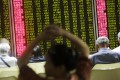 Investors look at screens showing stock market movements at a securities company in Beijing on Tuesday. Photo: EPA