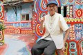 Huang Yung-fu posing for a photo next to his artwork in the Rainbow Village. Photo: AFP