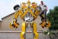 Welder Wang Liansheng poses with his version of the Transformer's character Bumblebee Autobot that he built for his in their backyard. Photo: ThePaper.cn