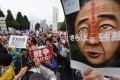 People shout slogans as they hold banners during an anti-government rally in front of the National Diet in Tokyo. Photo: AFP