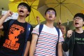 Joshua Wong, Alex Chow and Nathan Law chant slogans outside Eastern Court on Wednesday. Photo: Dickson Lee