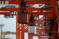 Cranes haul containers aboard ships in a port in Japan as the country seem to be showing signs of life amid a region wallowing in gloom. Photo: Reuters