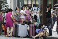 A group of Chinese tourists sit with their suitcases in the Ginza district of Tokyo, Japan, in August. Photo: Bloomberg