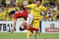 Guangzhou Evergrande midfielder Zheng Long, left, fights for the ball durjng an AFC Champions League quarterfinal match last month. Alibaba founder Jack Ma Yun bought 40 per cent of the team last year after getting drunk with its owner. He now has bigger plans for China's sports industry. Photo: AFP