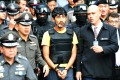 During the re-enactment, which was covered by a large media scrum, the suspect (centre) wore a bulletproof vest. Photo: Xinhua