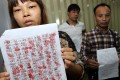Factory workers Qin Renfang (left) and Wang Qiang with a list of names of the workers at the mainland plant. Photo: Franke Tsang