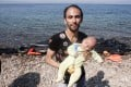 A man holds a baby as refugees arrive on the shore of Sykamias beach, west of the port city of Mytilini, after crossing the Aegean sea from Turkey. Photo: AFP