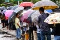 People queue for public transport in Ma On Shan during today's rainstorm. Photos: Sam Tsang/SCMP