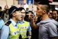 Police in Hong Kong have been accused in the past of failing to crackdown on triad activities. This file photo shows a typically tense scene between a police officer and a possible gang member. Photo: SCMP Pictures
