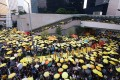Protesters hold yellow umbrellas outside the government offices in Admiralty. They stood silently for five minutes to reflect on the civil disobedience campaign. Photo: Sam Tsang