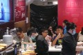 Diners continue with their meals although part of the McDonald's outlet - where the homeless woman died - was cordoned off with a black sheet on Sunday. Photo: SCMP Pictures