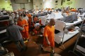 Inmates at a California state prison walk past their bunk beds in a gymnasium modified to house prisoners. The largest one-time release of federal prisoners starts this month in an effort to reduce overcrowding. Photo: AP