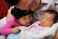 Chen Zhiguang, along with his daughter, holds and looks at his newly born son, the family's second child, in Nanjing. China has relaxed its family planning policy. Photo: Imaginechina