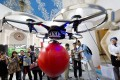 Visitors to the China Hobby Expo watch a drone controlled by a mobile phone fly in Beijing. Unmanned and remote-controlled aerial vehicles are gaining in popularity as prices drop and capabilities grow. Photo: AP