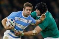 """Pumas winger Santiago """"Fluff"""" Cordero pushes past a tackle from Ireland's Mike ross. Photo: Reuters"""