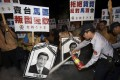A police officer puts out fire on the portraits of Chinese President Xi Jinping and Taiwan's President Ma Ying-jeou (right) during a protest against the upcoming Singapore meeting between Ma and Xi, outside Taipei Songshan airport on Saturday. Photo: Reuters