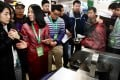 An exhibitor introduces a robot that can cook hundreds of dishes during the World Robot Conference in Beijing. Photo: Xinhua