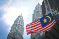 Malaysia's national flag flies in front of its landmark Petronas Twin Towers in Kuala Lumpur, Malaysia. photo: AP Photo/Vincent Thian
