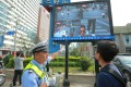 A policeman shows a man that he's been caught jaywalking on a screen besides a road in Shenyang. (Source: China Foto Press)