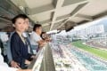 Privilege Club members watch the races from the balcony of the private member box at the Hong Kong Jockey Club Sha Tin Racecourse.