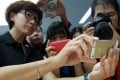 An Apple Store saleswoman holds a gold iPhone in Beijing on September 11, 2013. (Picture: SCMP)