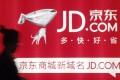 A woman walks past a advertisement board of Jingdong Mall (JD.com) in Nanjing, Jiangsu province in China. Photo: Rueters