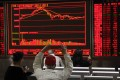 Investors monitor stock market data displayed on an electronic board at a securities brokerage house in Beijing, China. Photo: EPA