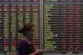 A woman walks past electronic boards showing share index at a bank in Kuala Lumpur, Malaysia. Photo: AP