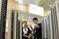 A sales assistant (R) speaks to a customer in front of a model of a residential complex, at a real estate exhibition in Shanghai, China. Photo: Reuters