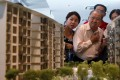 Prospective buyers look at a model of an upcoming suburban private condominium development during its launch in Singapore. Prices of Singapore's private homes fell for the eighth straight quarter due to government cooling measures. Photo: Reuters