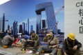 Construction workers have lunch outside a building site in Beijing, . Photo: Reuters