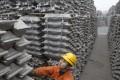 An employee checks aluminium ingots at Qingdao port in China. Photo: Reuters