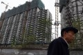 A man walks past a construction site for apartment buildings in Beijing. Photo: AFP