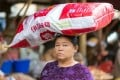A woman carrying a large monosodium glutamate bag on her head in the street of Mandalay, Myanmar