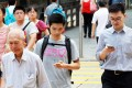 People using mobile devices on a street in Hong Kong. Picture: May Tse